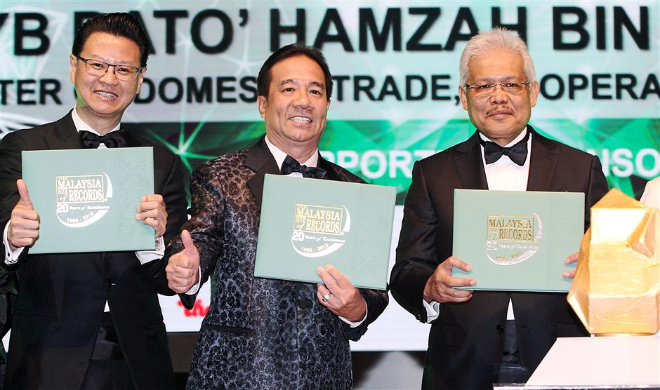 (From left) Tio, Ooi and Hamzah showing the Malaysia Book of Record coffeetable book.