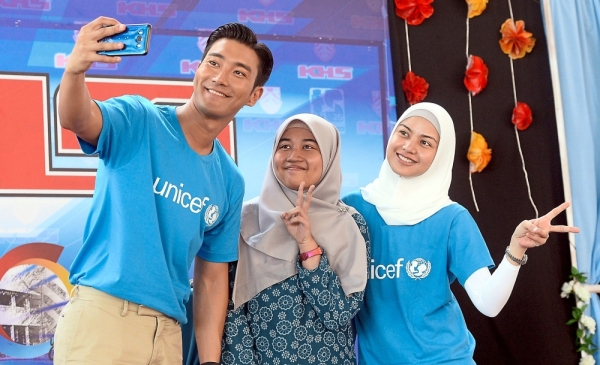 Spreading the cheer: Siwon and Lisa taking a wefie with a SMK Tinggi Kajang student during their visit to the school in Bandar Kajang. u2014 AZHAR MAHFOF/The Star