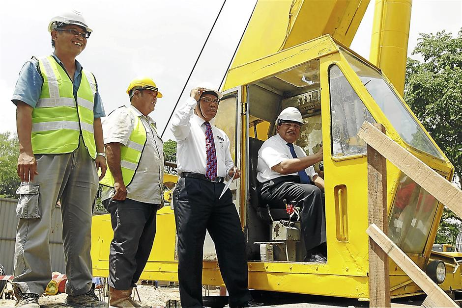 Tengku Adnan (in cab) accompanied by Phesal (third from left) launching Phase 2 of the Botanical Lake Garden upgrading project that includes the long awaited multi-storey carpark that is currently being built.
