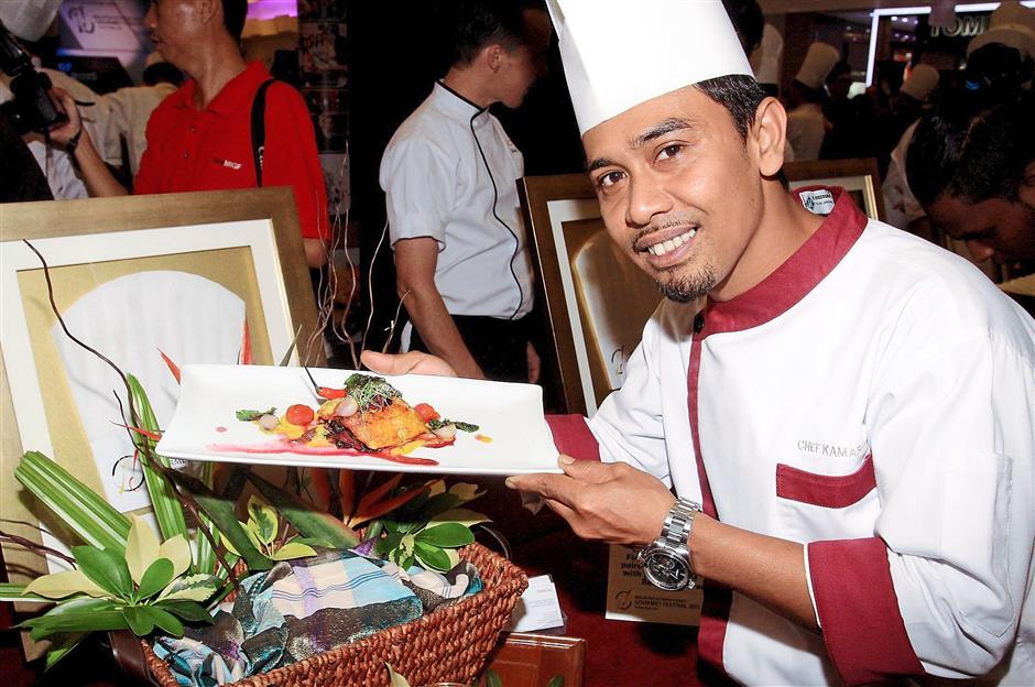 Enak KL chef Ahmad Kamaroull with his dish of Ikan Lemak Koma-Koma Pedas Cili Padi served with Red Spinach and topped with Fresh Curry Leaves.