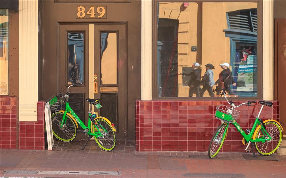 Two LimeBike bikes along 4th Avenue in downtown San Diego on March 1, 2018. (Eduardo Contreras/San Diego Union-Tribune/TNS)