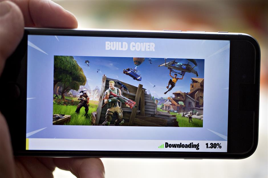 The Epic Games Inc. Fortnite: Battle Royale video game is displayed for a photograph on an Apple Inc. iPhone in Washington, D.C., U.S., on Thursday, May 10, 2018. Fortnite, the hitu00a0gameu00a0that\'s denting the stock prices of video-gameu00a0makers after signing up 45 million players, didn\'t really take off until it became free and a free-for-all. Photographer: Andrew Harrer/Bloomberg