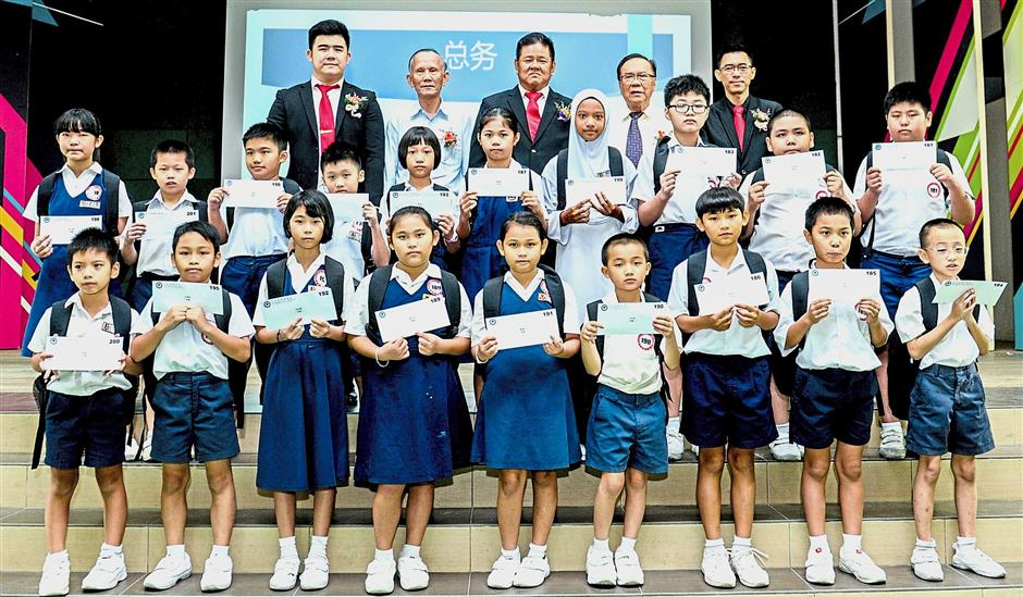 Peh (back row, centre) posing with some of the recipients during the presentation ceremony at SJKC Kim Sen in Jalan Kulim, Bukit Mertajam.