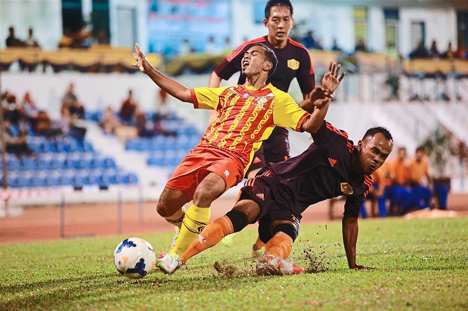 Progress denied: A Kubang Pasu player (yellow stripped shirt) being tackled by a JKR Kedah stopper during the K-League final at the UUM ground in Sintok, Kedah.