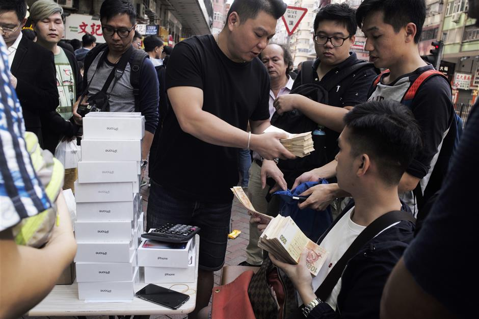 Unauthorized resellers buying newly-purchased Apple Inc. iPhone Xs from shoppers hold stacks of Hong Kong 1,000-dollar banknotes in the Mong Kok district of Hong Kong, China, on Friday, Nov. 3, 2017. It\'s onlyu00a0Day One, but the gray market trade in Apple\'s new iPhone is already in full swing in Hong Kong. Photographer: Justin Chin/Bloomberg