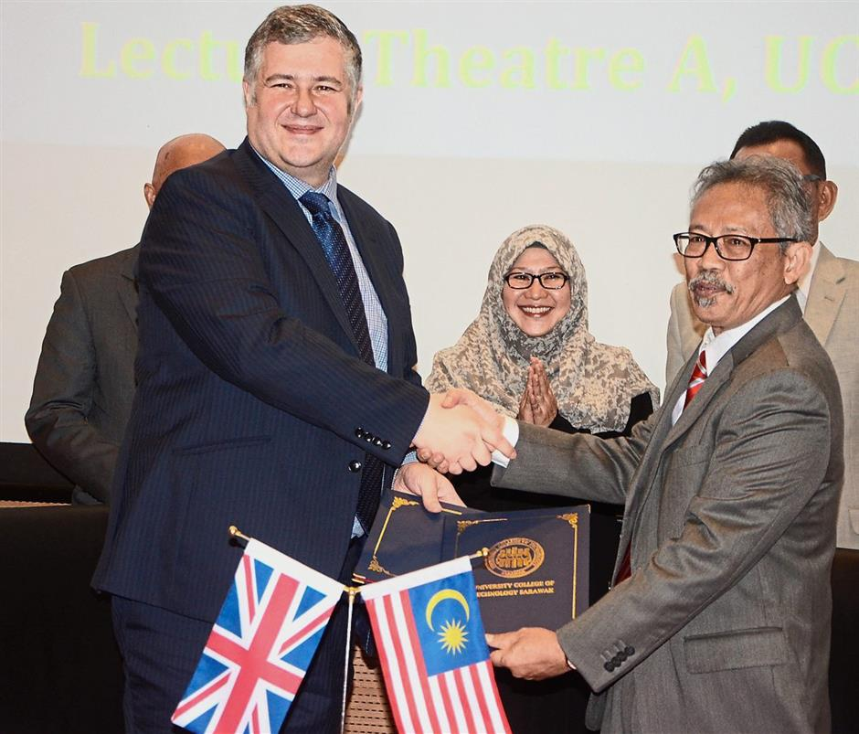 Prof. Clives exchanging the signed documents with Dr Sabarudin (right) at the event.