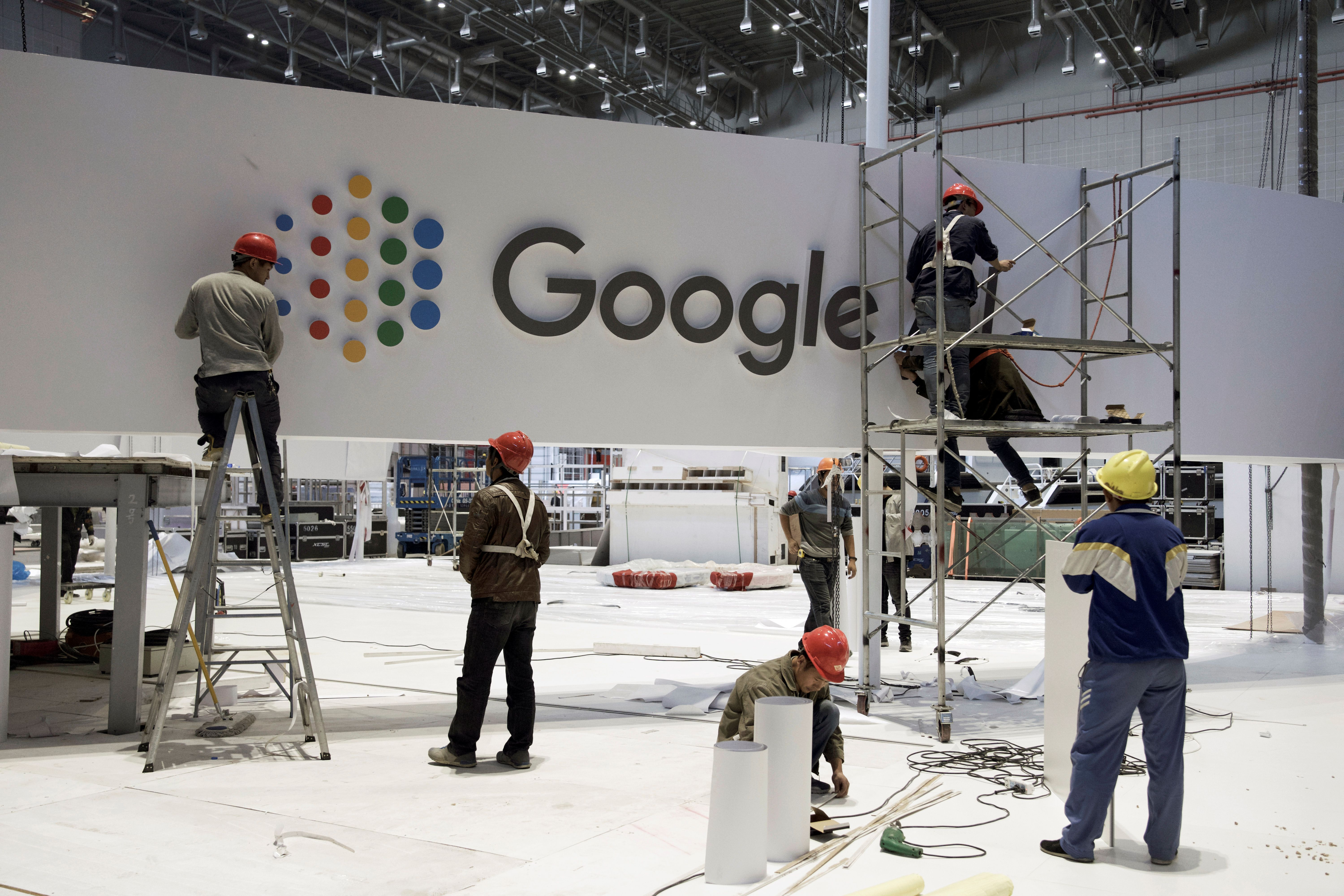 FILE PHOTO: Workers set up the booth for Alphabet Inc\'s Google inside the National Exhibition and Convention Center, the venue for the upcoming China International Import Expo (CIIE), in Shanghai, China October 28, 2018. China Daily via REUTERS