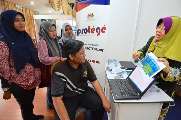 Empowering the youth: Norashikin (right) explaining to Eizul Aiman the eight flagship programmes under Protu00e9gu00e9 during the UiTM Career and Industrial Relations Expo.