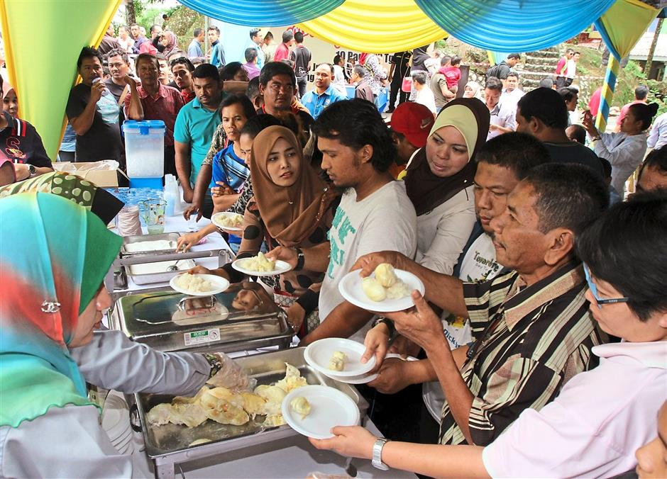 A large crowd helping themselves to the durians served with pulut and sugar at Anjung Indah in Balik Pulau.