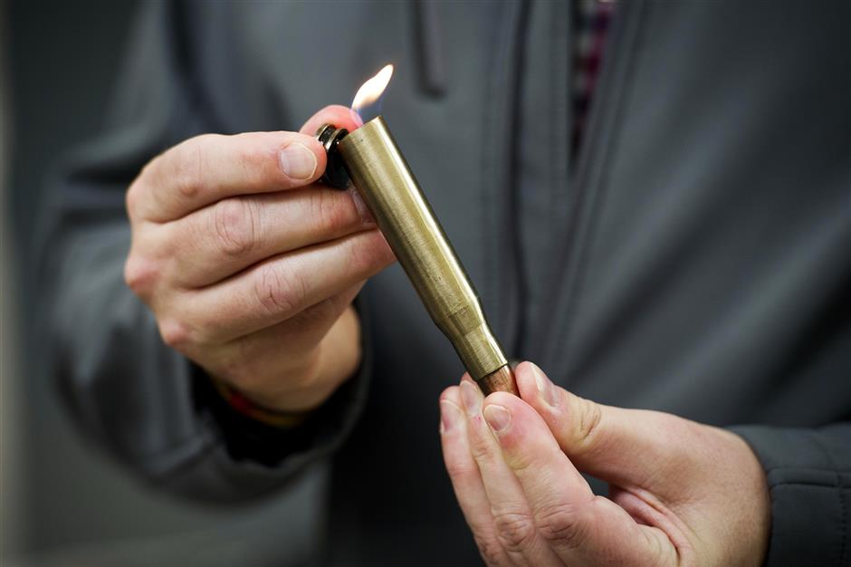David Johnston, TSA's social media director, displays a lighter mounted inside of a bullet casing which was confiscated from a passenger at a Transportation Security Administration (TSA) checkpoint at Dulles International Airport in Dulles, Va., Tuesday, March 26, 2019. TSA's social media presence has been something of a model for other federal agencies _ striking a tone is humorous, but still gives travelers informational dos and don'ts. (AP Photo/Cliff Owen)