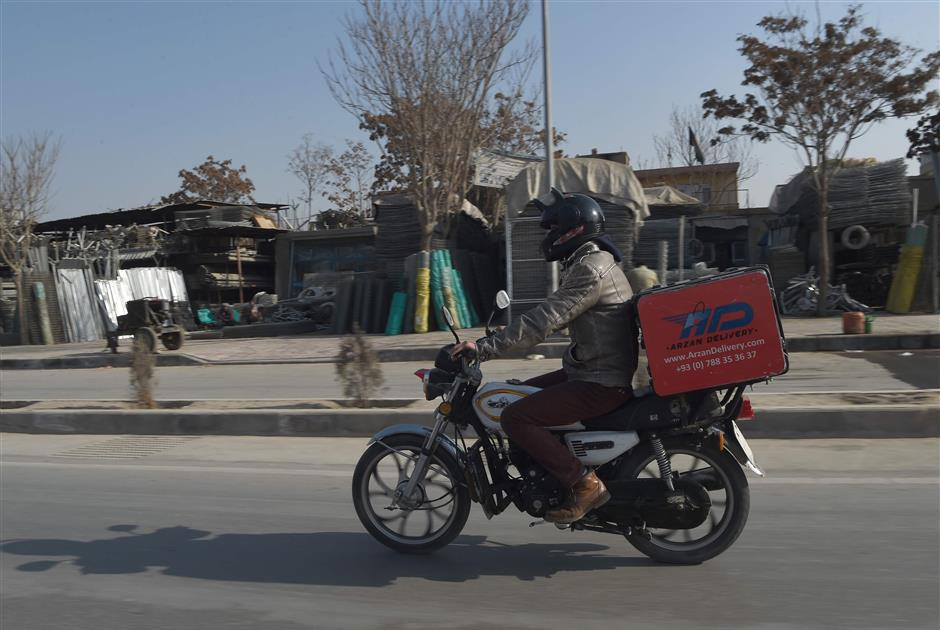 In this photo taken on January 16, 2018 Afghan courier Sarajuddin rides a motorbike on a street in Kabul. As Afghans embrace online shopping, harried delivery men in the capital are increasingly running the gauntlet of security checkpoints, gridlocked traffic, and potholed roads -- as well as the near-constant threat of blasts and attacks. / AFP PHOTO / WAKIL KOHSAR / TO GO WITH Afghanistan-economy-technology-unrest,FOCUS by Usman Sharifi