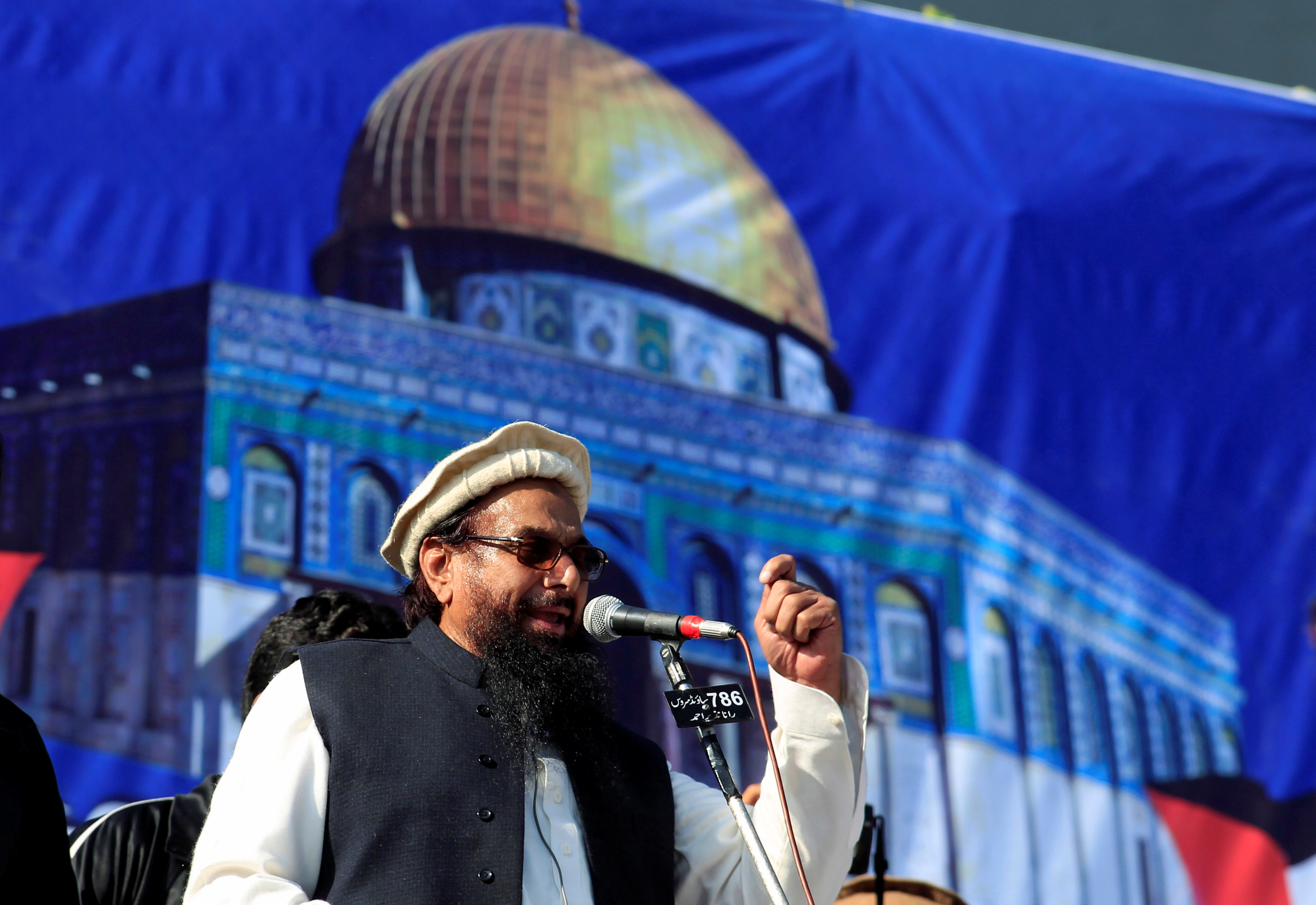 FILE PHOTO: Hafiz Muhammad Saeed (C), chief of the Islamic charity organisation Jamaat-ud-Dawa (JuD), speaks to supporters during a gathering to protest against Trump's decision to recognise Jerusalem as the capital of Israel, in Rawalpindi, Pakistan December 29, 2017. REUTERS/Faisal Mahmood