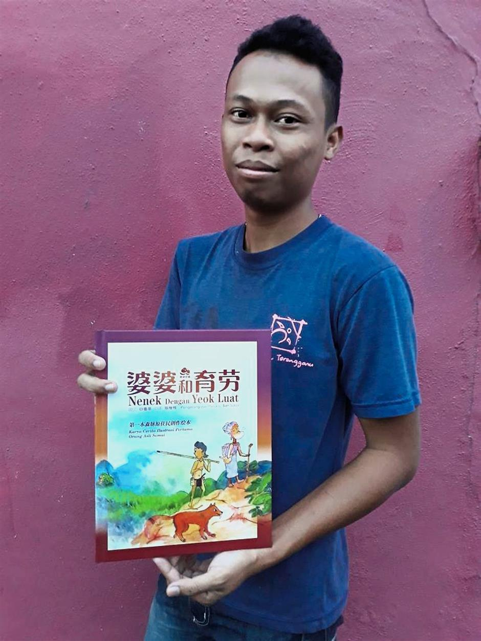 Tribal writer: Saluji with his book 'Nenek dengan Yeok Luat' published in Malay and Chinese at the Shah Alam National Botanic Park.