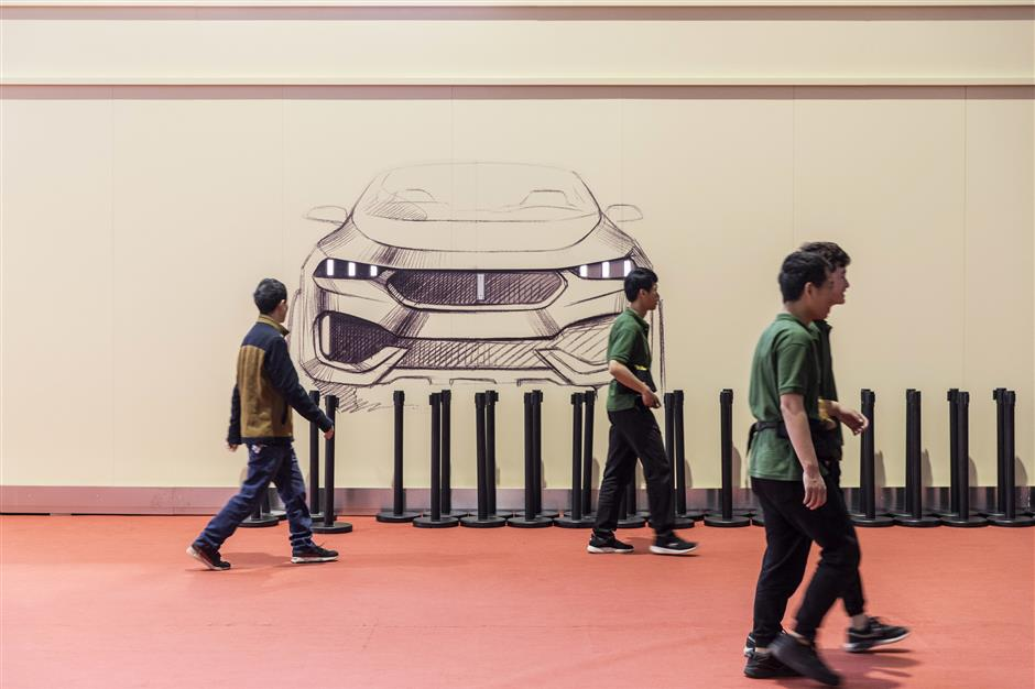 Attendees walk past a sketch of a WEY brand vehicle on display at the Auto Shanghai 2019 show in Shanghai, China, on Wednesday, April 17, 2019. China\'s annual auto show, held inu00a0Shanghaiu00a0this year, opened to the media on April 16 amid the specter of an electric-caru00a0bubbleu00a0and as the world\'s largest auto market trudges through its first recession in a generation. Photographer: Qilai Shen/Bloomberg