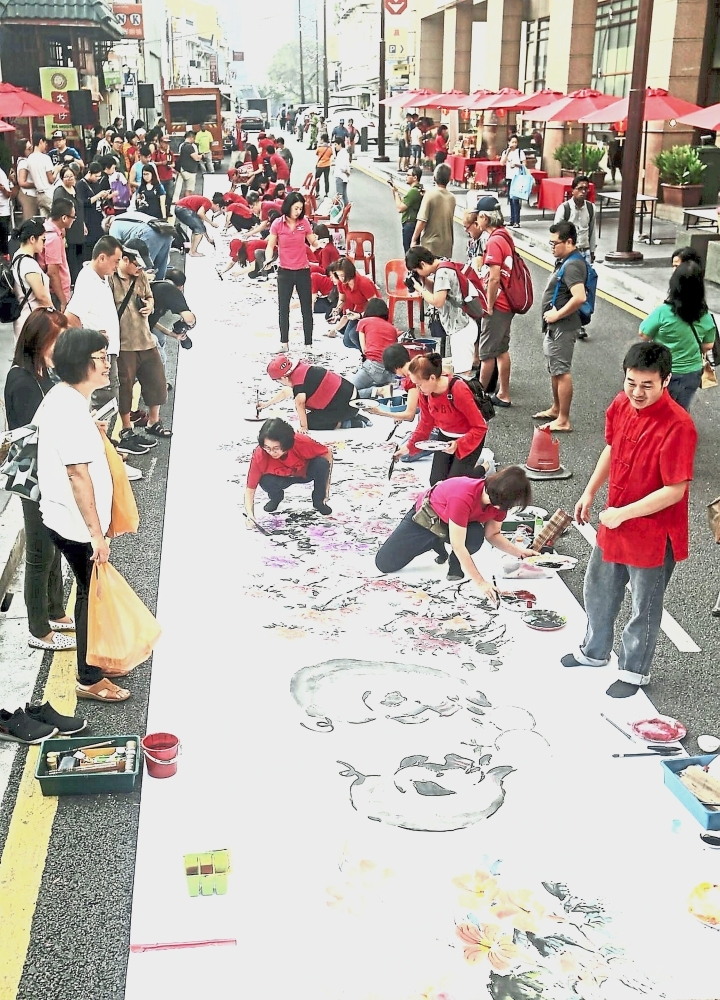 More than 30 artists came together to complete the 36m-long painting of peonies and pigs.