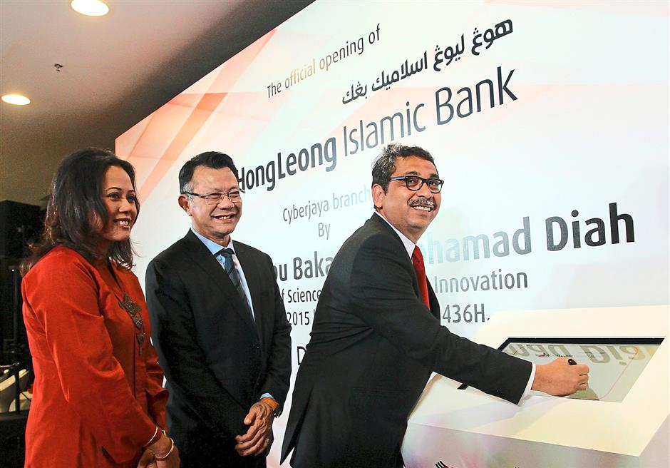 New frontier: Abu Bakar (right) launching Hong Leong Islamic Bank's new concept branch in Cyberjaya with a digital signature. Looking on are Raja Teh Maimunah (left) and Hong Leong Bank chief executive officer and group managing director Tan Kong Khoon.
