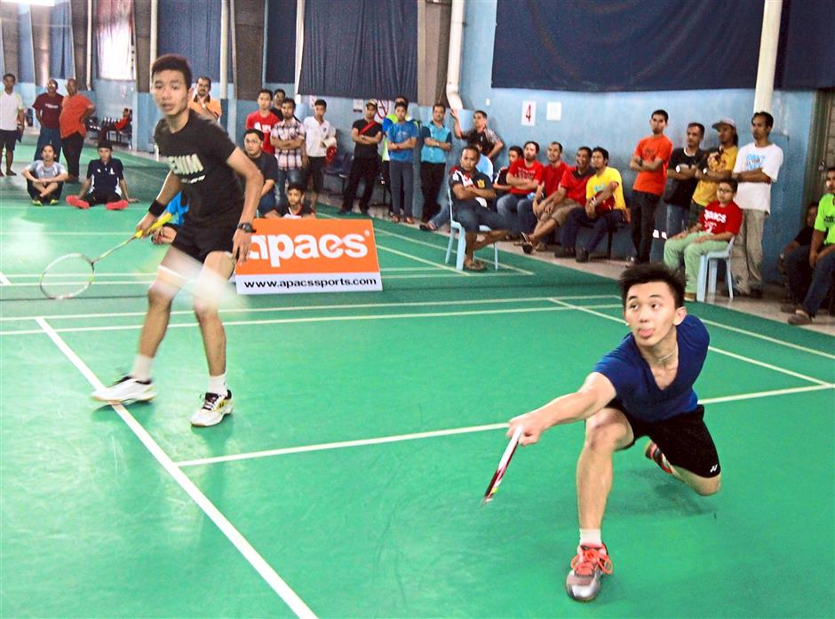 Zi Heng (right) retrieving the shuttlecock while his partner looks on during the finals of the boys' Under-16 doubles. They beat Umar Al Qhattab-Asmawi Udin 21-17,19-21, 22-20 to emerge champions.