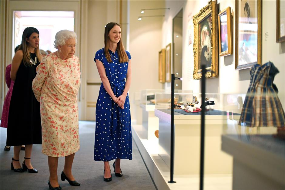 Britain's Queen Elizabeth II looks at a dress worn by Albert Edward, Prince of Wales (later King Edward VII) alongside Lucy Peter, assistant curator, as part of the exhibition to mark the 200th anniversary of the birth of Queen Victoria for the Summer Opening of Buckingham Palace, in London, Britain, July 17, 2019. Victoria Jones/Pool via REUTERS