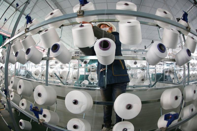 A Jan 9, 2013 picture showing a woman working in a textile factory in Jiangxi that exports clothing materials to the US and Europe. A Reuters poll of economists indicates that China\'s manufacturing activity in October likely grew at its fastest rate since April 2012 - AFP Photo.