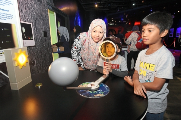Ismayati Ismail, 35, and her children experiencing one of the exhibits in the Space area.