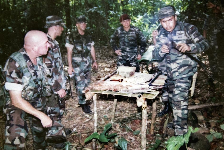 Keeping a close watch: Toh (in red beret) looking on ?during a jungle operation. Inset: Toh in his official uniform.