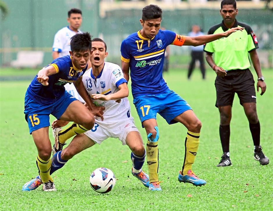 Juniors vs seniors: Two President Cup players (in blue) putting pressure on their opponent during the friendly match against the Penang state side. The seniors won 3-0.
