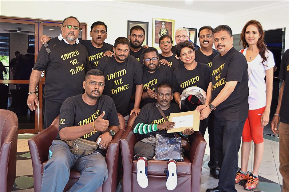 Esvaran (seated, right) receiving the donation for the three-wheel motorcycle raised during the 'United We Dance' Zumba fitness party from Dr Manohur and Asvika (second row, second from right).