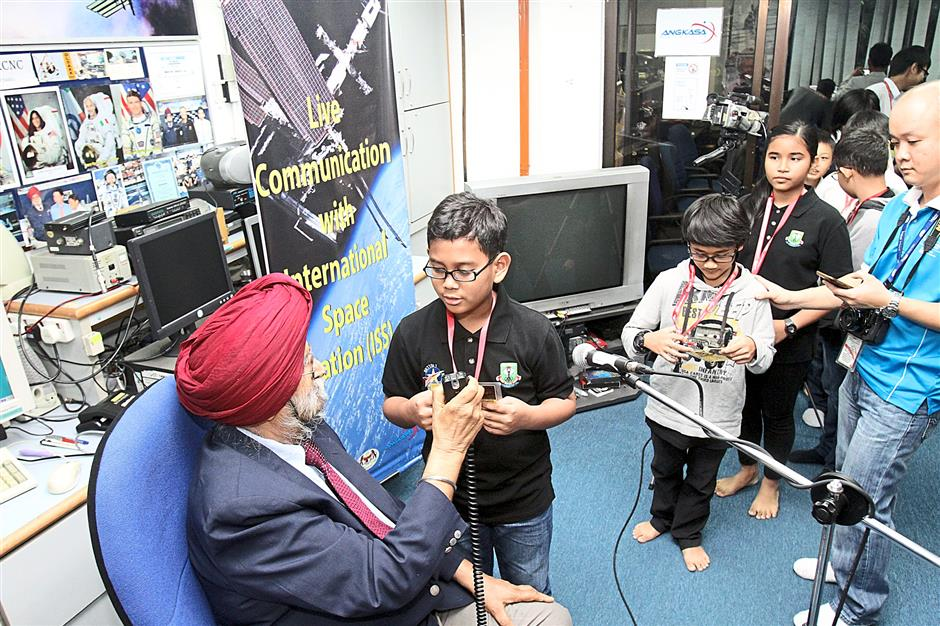 Taman Tun Dr Ismail 1 pupil Zarif Zairul Azreen, 10, posing a question via live radio contact.