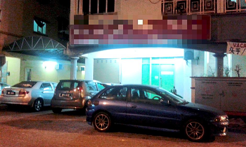 Many vehicles are seen parked at the entertainment outlets located along Jalan PJS3/48 at night.
