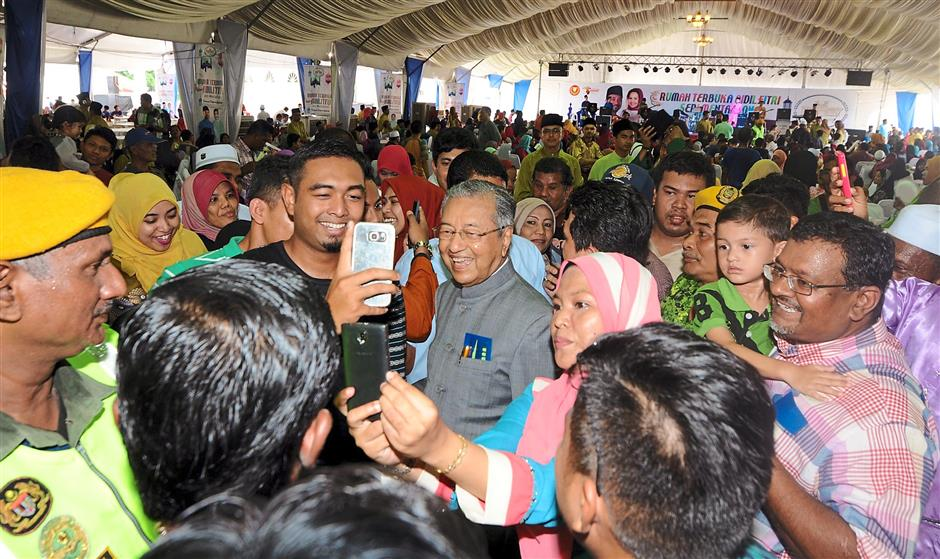 Dr Mahathir is surrounded by visitors as he arrives at the open house.