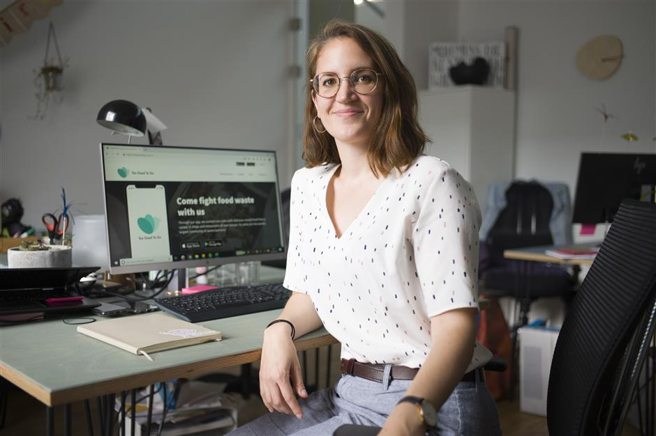 In this Tuesday, May 21, 2019 photo, Franziska Lienert spokeswoman of the company which runs the food sharing app 'Too Good To Go', poses for a photo at her working desk during an interview with the Associated Press in Berlin. In Germany, growing numbers of people use modern technology such as phone apps to help reduce food waste. In an effort to cut down on climate-wrecking carbon dioxide emissions created by food waste, they build online communities to share food before throwing it away. (AP Photo/Markus Schreiber)