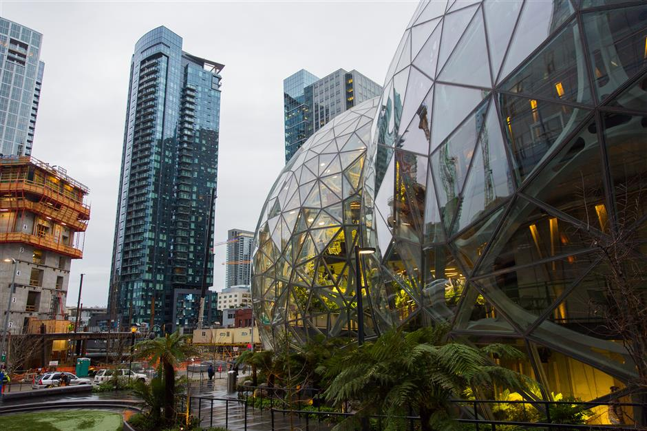 The Amazon.com Inc. Spheres, right, stand during opening day ceremonies at the company's campus in Seattle, Washington, U.S., on Monday, Jan. 29, 2018. The Spheres, a new gathering and working space for Amazon employees located in the heart of the downtown Seattle Amazon campus, contains hundreds of plant species from cloud rainforest environments around the globe, and maintains a tropical climate similar to Costa Rica or Indonesia. Photographer: Mike Kane/Bloomberg