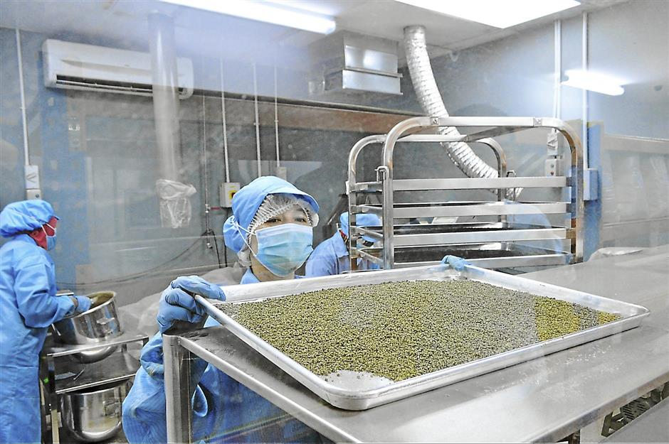 A clean room worker shows off a tray of dried tea leaves at the RM 10 million factory in the plantation.