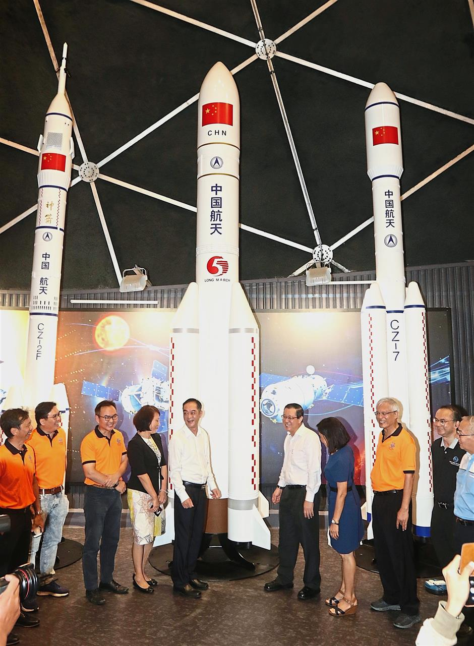 Lim and Wu Jun (both in white) sharing a light moment as they visit the preview set up of the rockets donated by China Science and Technology Museum to Tech Dome Penang in Komtar, Penang. — Photos: ZHAFARAN NASIB/The Star