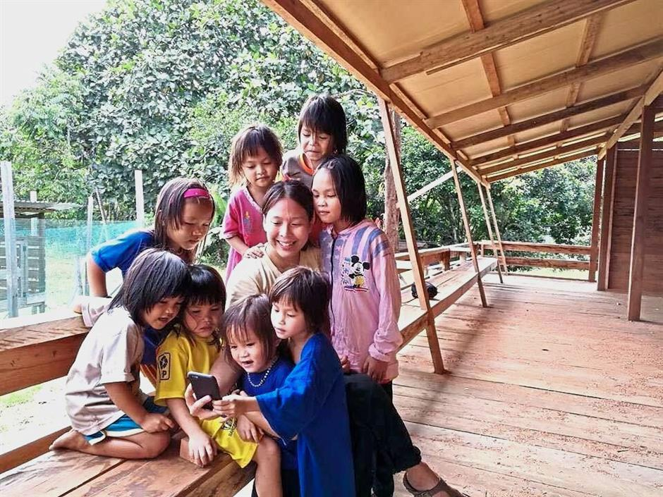 Wonderment: ufeffChan showing a smartphone to Penan children at the new kindergarten building.