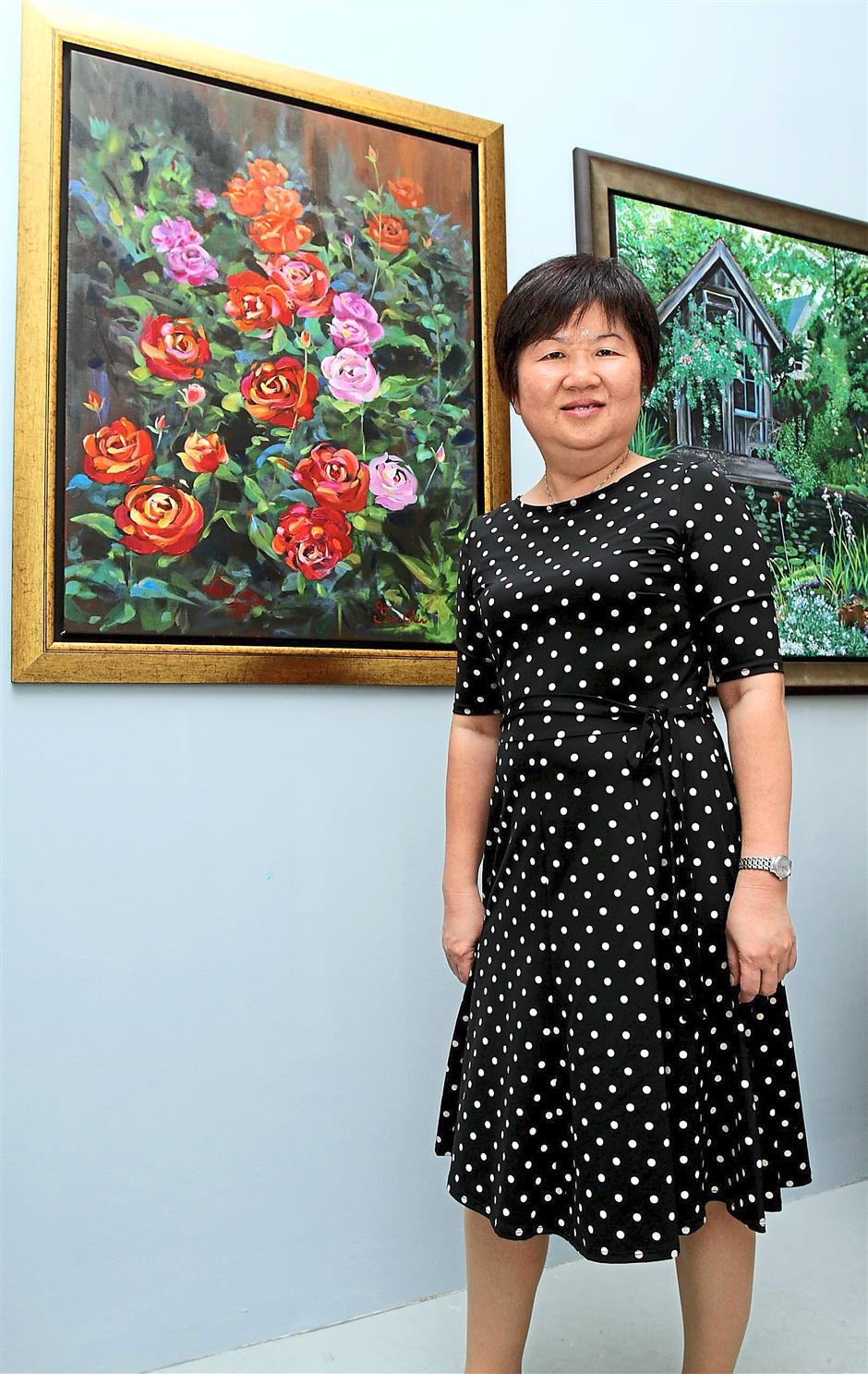 Simply lovely: Yee (right) showing her acrylic paintings that feature landscape and flowers.