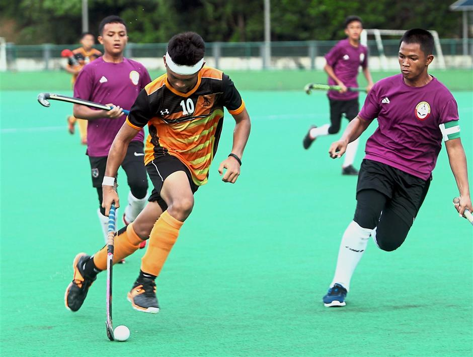A Kuala Selangor player (in orange) dribbling away from his Kuala Langat opponent in the Division Five final. Kuala Langat are champions of Division Five.