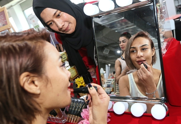 Sunshine Aileen (left) trying out the lipsticks available at the Heidaia Beauty booth.