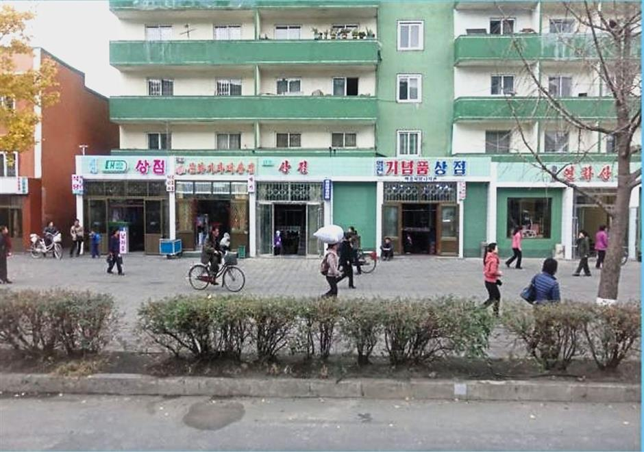 Budding entrepreneurship: Shops with electric signs lined up on a street in North Korea. More people are making a living through commercial activities. — The Korea Herald