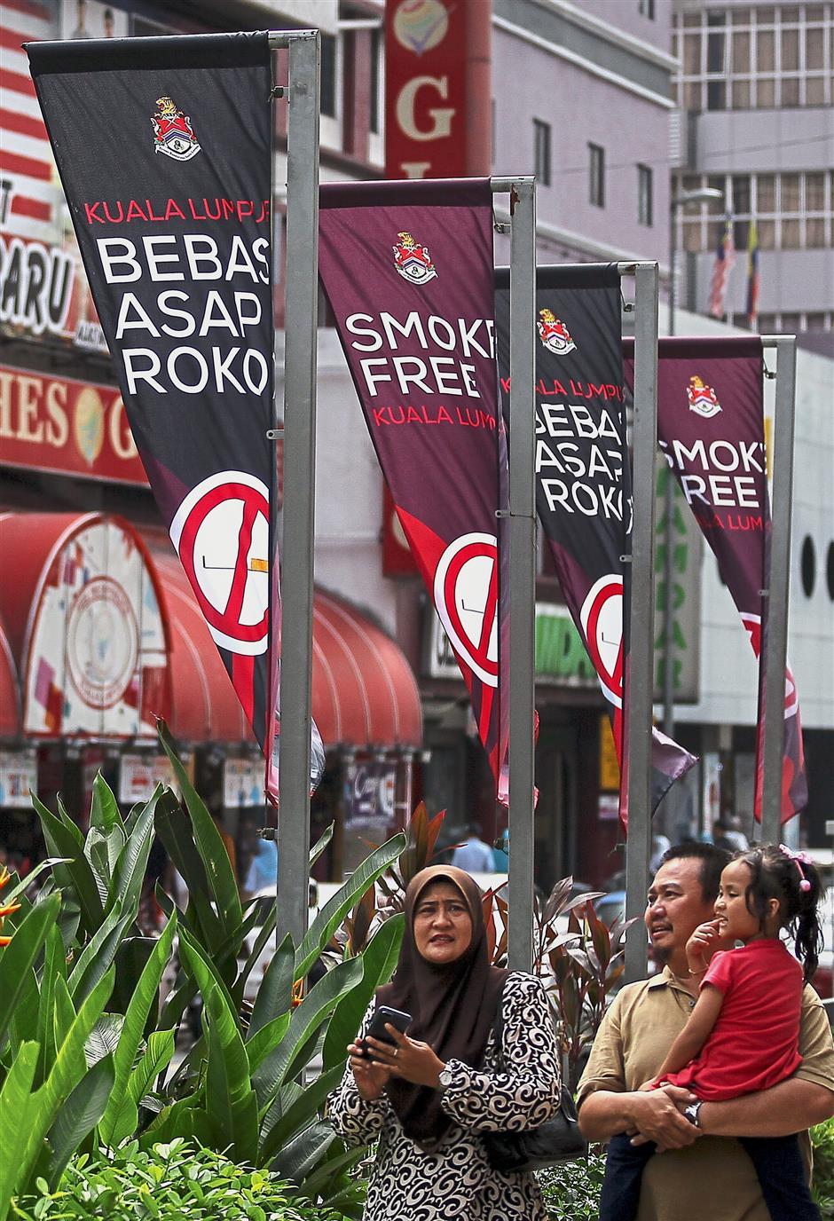 Raising awareness: People walking pass 'Smoke-free Kuala Lumpur' banners along a walkway in Kuala Lumpur. — Bernama