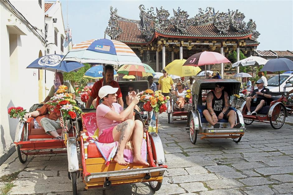 Tourists exploring George Town on trishaw.