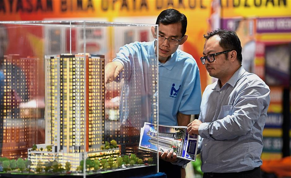 A file image of a salesman explaining features of PR1MA housing project to a customer. One of the main thrusts in the BN manifesto is to build more affordable housing. – Bernama