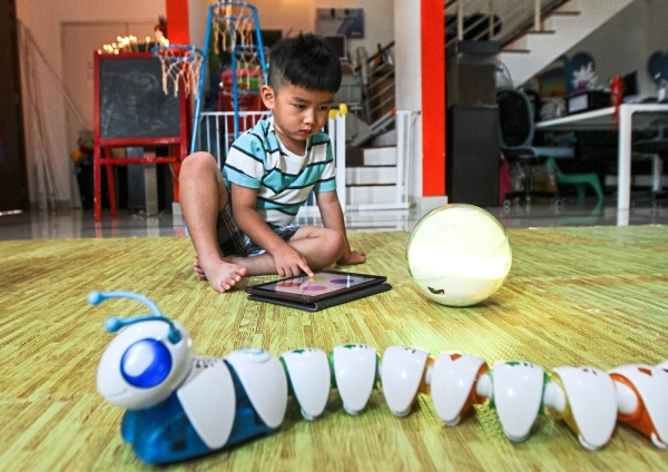 Young Khew playing with the robotic toys at Animals for Young. —  Photos: MOHD SAHAR MISNI/The Star