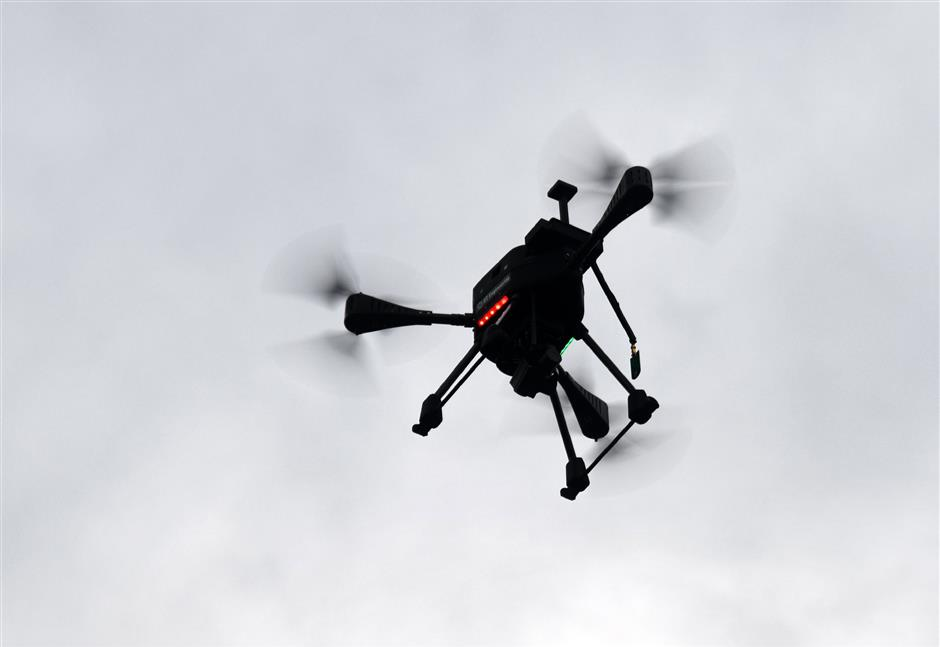 This photo taken on October 17, 2018 shows a drone owned by Singapore Technologies Aerospace during a demonstration in Singapore. - Hi-tech Singapore is planning to roll out a swarm of drones for tasks that include delivering parcels, inspecting buildings and providing security, but safety and privacy concerns mean the initiative may hit turbulence. (Photo by Roslan RAHMAN / AFP) / TO GO WITH STORY: Singapore-drones-technology, FOCUS by Martin ABBUGAO