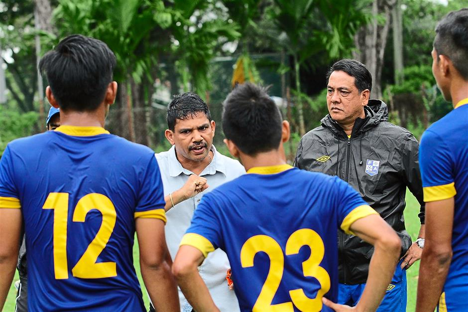 Motivating his team: Veloo (in white) delivering a pep talk to the players before the friendly against the Penang state side at the Penang Sports Club. WIth them is Zabidi (in black).