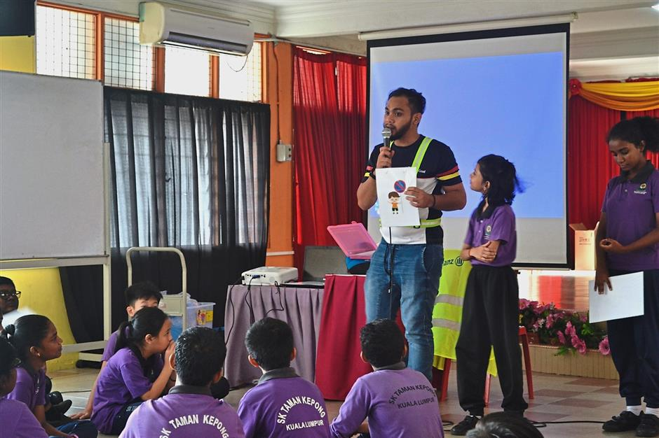 Allianz employee Zharif Abu Safian (standing, left) explains to SK Taman Kepong students about basic road safety rules and traffic signage to adhere to during the road safety programme.