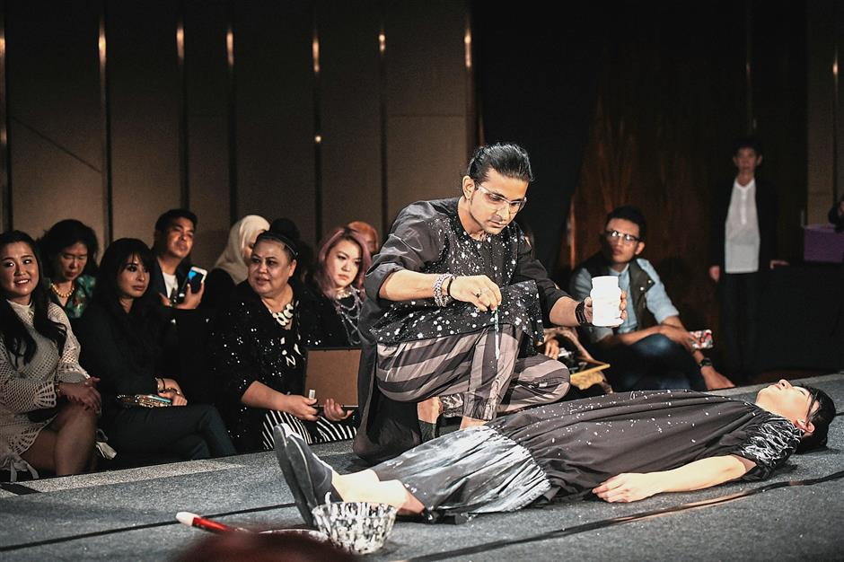 Ritesh painting a dress live on the runway while his works are showcased on stage.