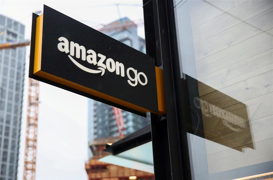 FILE PHOTO: A sign for the new Amazon Go store on 7th Avenue at Amazon\'s Seattle headquarters in Seattle, Washington, U.S., January 29, 2018.   REUTERS/Lindsey Wasson/File Photo