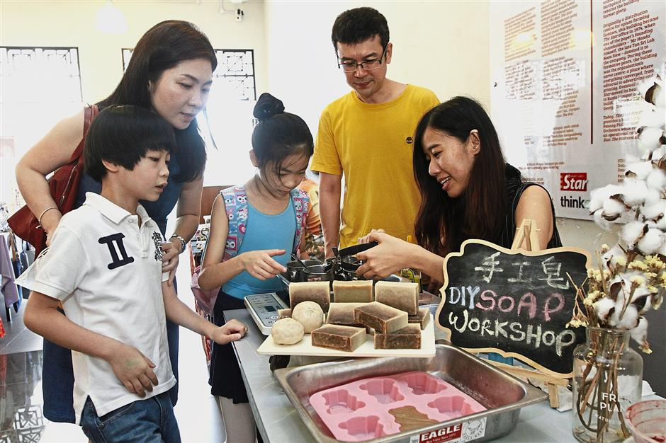 Wong (right) showing the DIY Soap to her customers (from left) Edmund Lim, 6, Agnes Ooi, 41, Emily Lim, 9, and Michael Chong, 43.