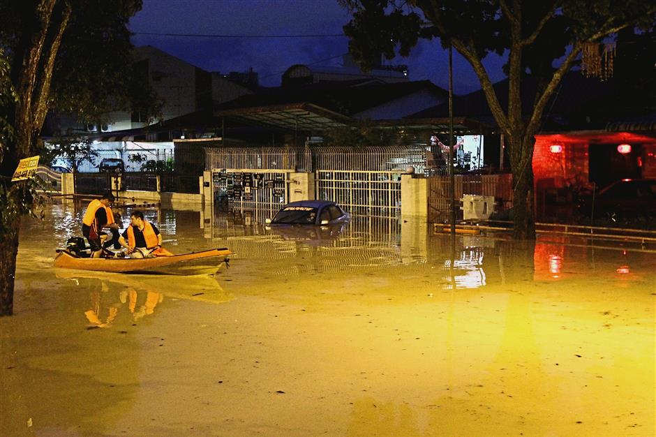 The state Fire and Rescue Department personnel monitoring the situation on a boat and helping rescue those stuck in the floods along Jalan P. Ramlee.